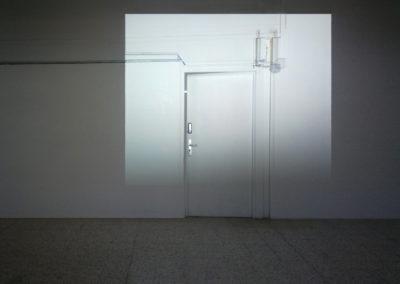 Flore Saunois, L'ombre d'un doute, 2017, installation in situ, dimensions variables, photographie vidéo-projetée . Vue d'exposition: Die Nacht des Augenblicks, Institut Français, Hambourg, Allemagne, 2019. Photographie d'une porte entr'ouverte, projetée à échelle 1 sur cette même porte, alors fermée. | art-cade*